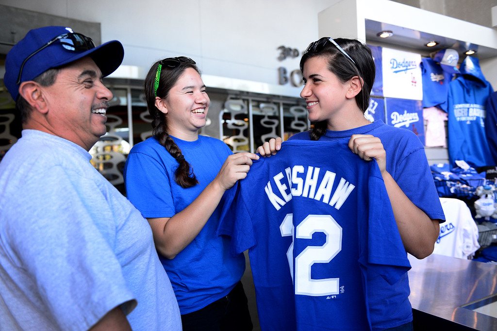 . Amanda Barroso, 17, of Oxnard, shops for a Clayton Kershaw shirt with her father David and friend Ashley Ontiveros, 18, before the Dodgers vs Brave\'s game 3 of the NLDS at Dodger Stadium, Sunday, October 6, 2013. (Photo by Sarah Reingewirtz/Los Angeles Daily News)