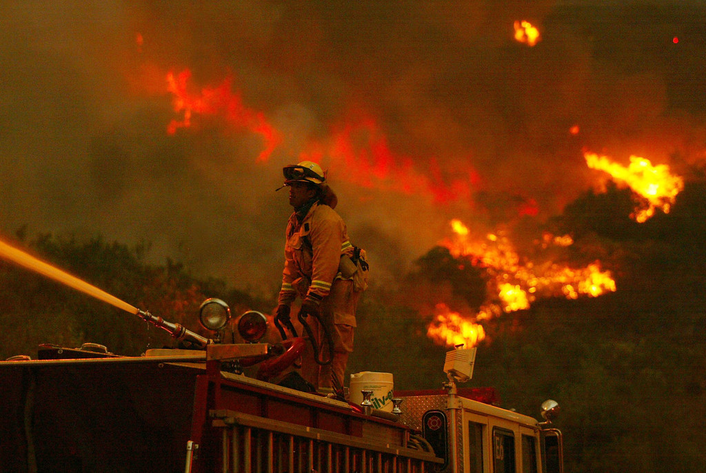 . SAN DIEGO - OCTOBER 27:  A San Jose firefighter battles a portion of the Cedar Fire using a water spout from atop a firetruck October 27, 2003 near Lakeside in San Diego, California. The death toll stands at 13, with more than 1,000 homes being reduced to ashes as southern California fires continue to burn. Winds have eased a bit, but 30,000 homes remain threatened by the fires, which have charred more than 400,000 acres, according to officials. Davis, who has activated the National Guard, predicted damages will be in the billions of dollars.  (Photo by Donald Miralle/Getty Images)