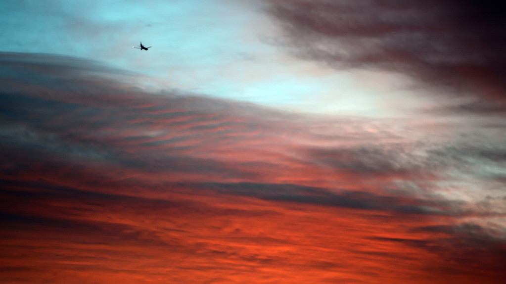 . A plane flies west at sunset prior to a prep basketball game between San Dimas and Wilson at Wilson High School in Hacienda Heights, Calif., on Friday, Jan. 31, 2014. (Keith Birmingham Pasadena Star-News)