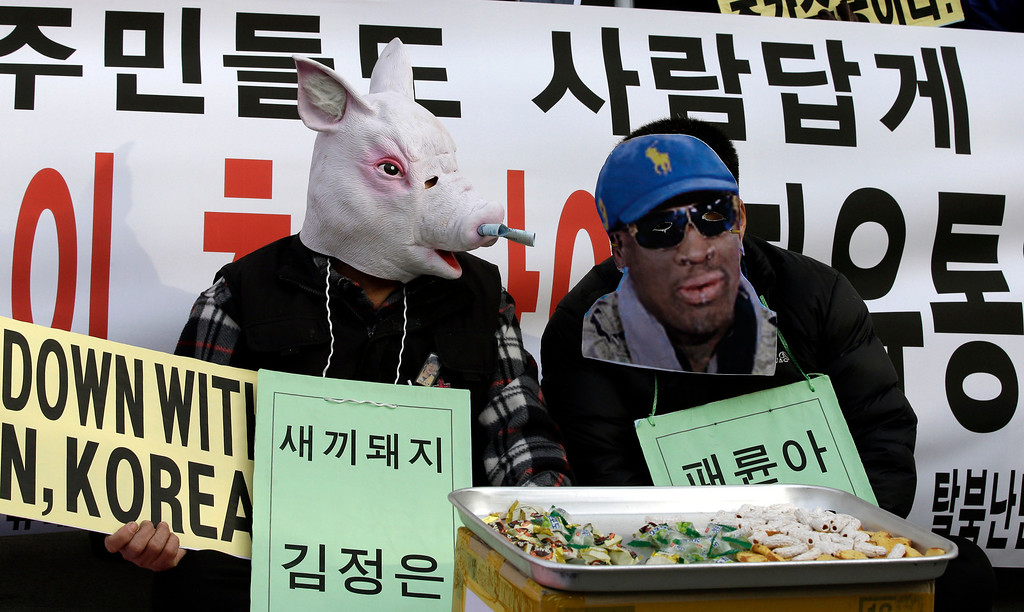 """. A protester wearing a mask of a pig depicting North Korean leader Kim Jong Un, left, and another wearing a mask of former NBA player Dennis Rodman, who is currently in Pyongyang with fellow former NBA players for a basketball game against a team of North Koreans, perform during an anti-North Korea rally on what is believed to be the birthday of  Kim, in Seoul, South Korea, Wednesday, Jan. 8, 2014. More than 100 anti-North Korea protesters and North Korean defectors attended the rally denouncing the North\'s human rights record and nuclear tests. The writing on the left reads \""""Little pig, Kim Jong Un.\"""" (AP Photo/Lee Jin-man)"""