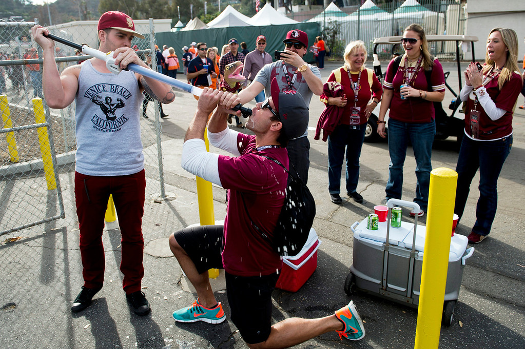 . Florida fans Morgan Strongberg, 31, of Colusa, guzzles down beer from a beer bong from Brandon Langdon, 24, of Rhode Island, before the BCS National Championship game at the Rose Bowl in Pasadena Calif. on Monday, Jan. 6, 2014. (Watchara Phomicinda/ Pasadena Star-News)