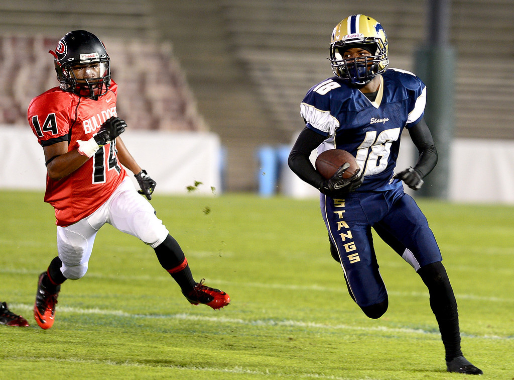 . Pasadena\'s Sean McDuffie (14) trails Muir \'s Taeon Mason (18) as he goes for a punt return touchdown in the annual Turkey Tussle Friday night, November 8, 2013 at the Rose Bowl in Pasadena. (Photo by Sarah Reingewirtz/Pasadena Star-News)