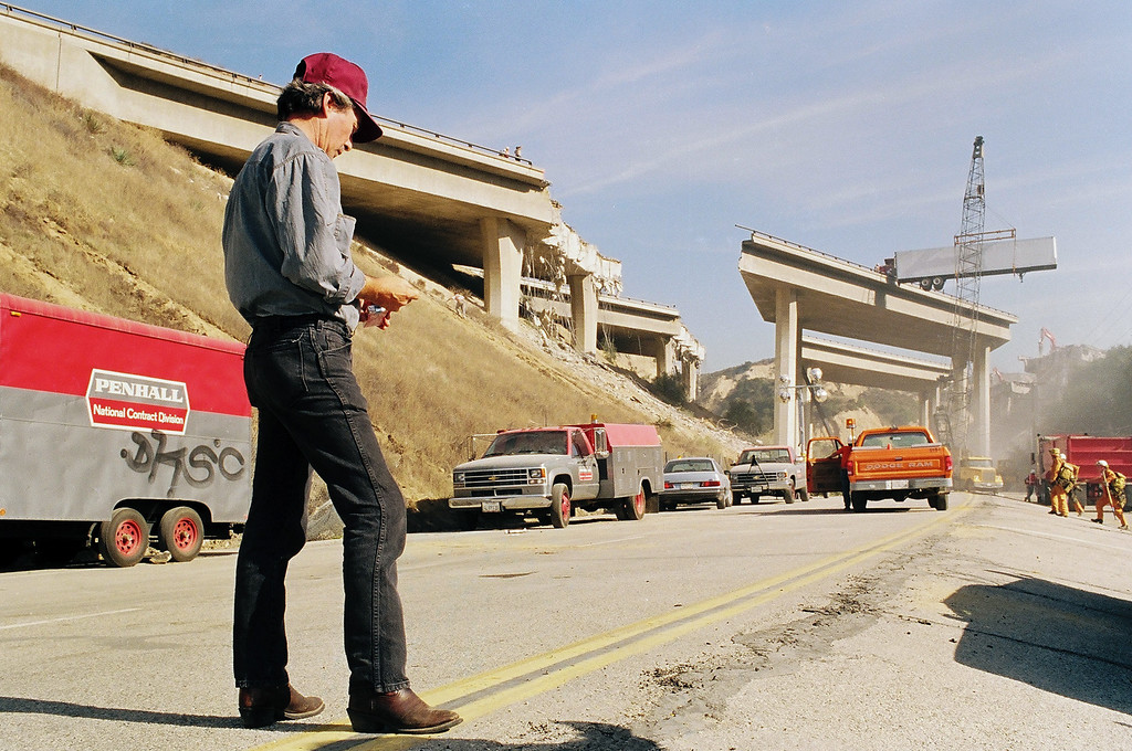. Truck driver Ervin Nichols of Bend, Oregon, waits as his truck is lowered from the shattered Golden State Freeway in Newhall two days after the quake. While Nichols was able to make his way off the freeway when the shaking stopped, his truck was left stranded on the overpass. (Photo by David Crane/L.A. Daily News)