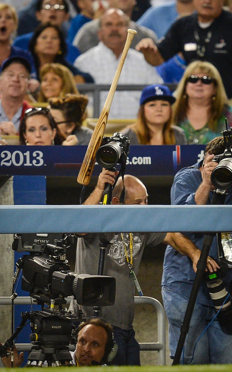 . Los Angeles Daily News photographer Andy Holzman gets hit by a flying bat in the third base well during game action in NLCS game 3 at Dodger stadium Monday, October 14, 2013 ( Photo by Hans Gutknecht/Los Angeles Daily News )