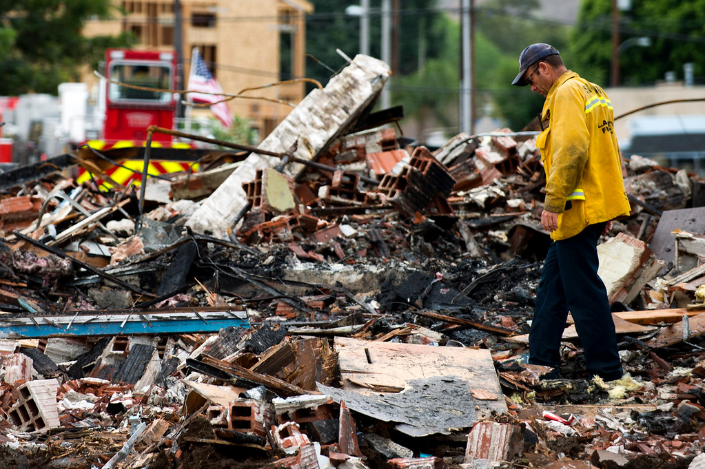. A firefighter looks through the debris of a destroyed warehouse after a 3-alarm fire near 9th Avenue and Clark Avenue in City of Industry on Wednesday, July 10, 2013. (SGVN/Staff Photo by Watchara Phomicinda)