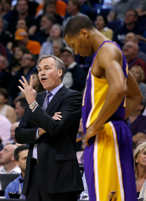 . Los Angeles Lakers coach Mike D\'Antoni, left, argues with referees as Wesley Johnson, right, listens during the second half of an NBA basketball game against the Phoenix Suns on Wednesday, Jan. 15, 2014, in Phoenix. The Suns defeated the Lakers 121-114. (AP Photo/Ross D. Franklin)