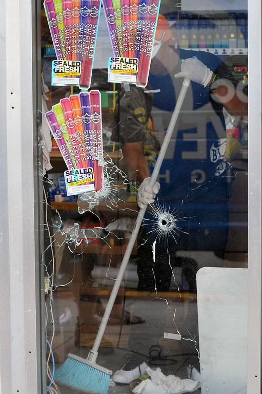 . A worker sweeps broken glass inside IV Deli Mart on Pardall Road in Isla Vista, Saturday, May 24, 2014, from Friday night\'s shootings. (Photo by Michael Owen Baker/Los Angeles Daily News)
