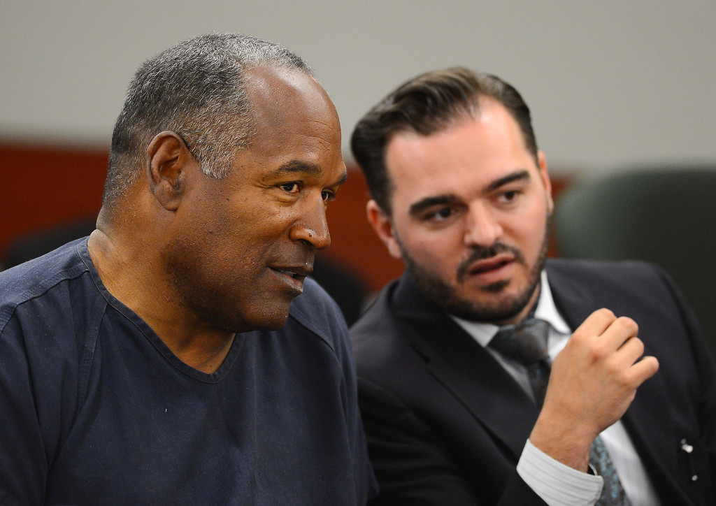 . O.J. Simpson, left,  confers with defense team member Dustin Marcello during an evidentiary hearing in Clark County District Court in Las Vegas Tuesday, May 14, 2013. Simpson appeared in court seeking a new trial in a Las Vegas armed robbery conviction.  (AP Photo/ETHAN MILLER, Pool)