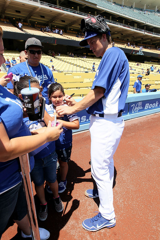 . Pitcher Zack Greinke #21 of the Los Angeles Dodgers signs an autograph for a fan prior to  the MLB game against the Miami Marlins at Dodger Stadium on May 12, 2013 in Los Angeles, California.  (Photo by Victor Decolongon/Getty Images)
