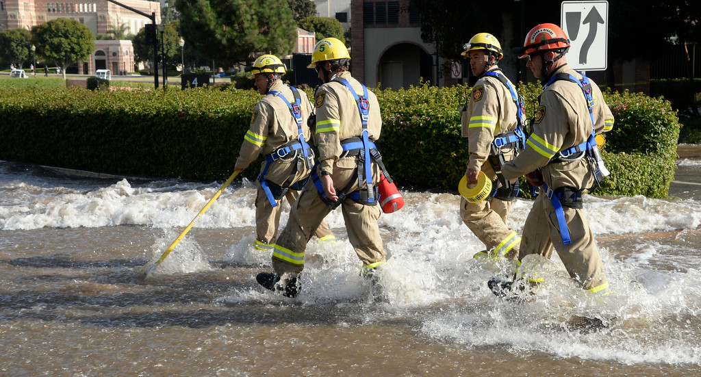 . July 29,2014. Westwood CA,  L.A. city firefighters make their way through a river of water after a major water main break sent a geyser of water blasting through Sunset Boulevard north of the UCLA campus Tuesday, sending mud and water cascading down the street and inundating a number of vehicles as it made its way onto the campus. Photo by Gene Blevins/LA DailyNews