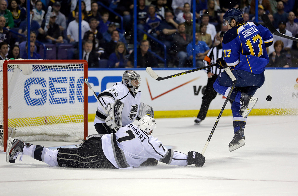 . St. Louis Blues\' Vladimir Sobotka, of the Czech Republic, is hit by the puck as Los Angeles Kings\' Rob Scuderi, front left, and goalie Jonathan Quick watch during the second period in Game 5 of a first-round NHL hockey Stanley Cup playoff series, Wednesday, May 8, 2013, in St. Louis. (AP Photo/Jeff Roberson)