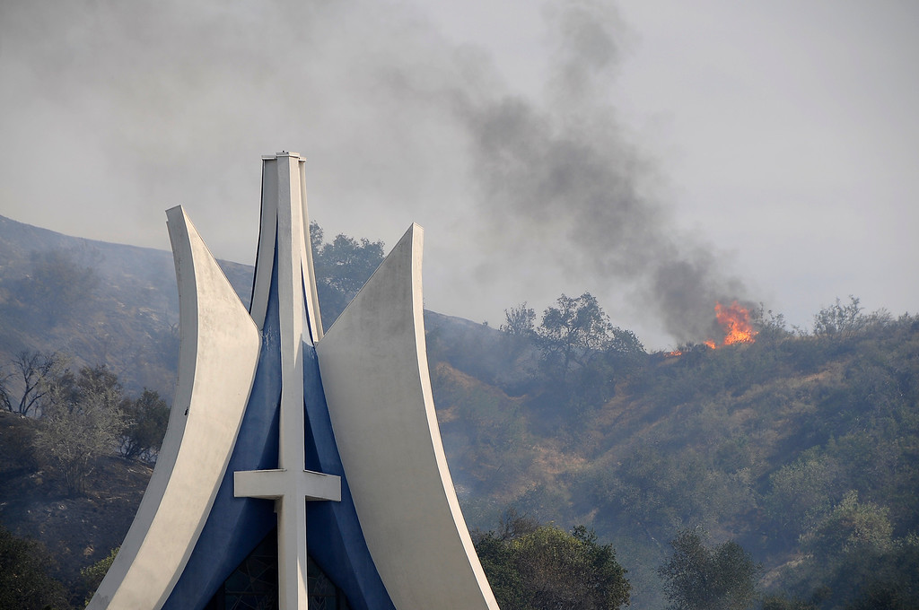 . A fire looms up on the mountains behind the Self Realization Fellowship Glendale Temple on East Chevy Chase Dr. A brush fire burned nearly 75 acres in an area north and east of the 134 and 2 freeways in Glendale. Residents on East Chevy Chase, east of the 2 freeway were evacuated as helicopters, hand crews and firefighters battled the fire that burned through the mountains and canyons. Glendale, CA 5/3/2013(John McCoy/Staff Photographer)