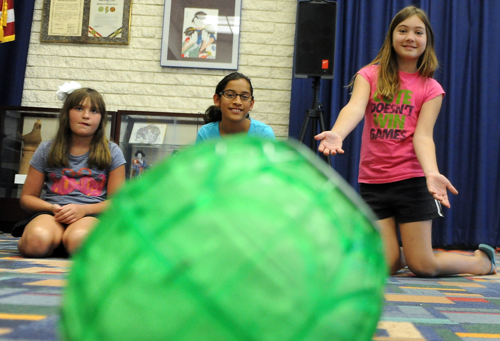 . Ten year-old Kayla Scoria, right, rolls the ice cream ball during a Summer Teen Reading Club ice-cream making and tasting session at the Glendora Public Library Bidwell Forum on Wednesday, July 17, 2013 in Glendora, Calif.   (Keith Birmingham/Pasadena Star-News)