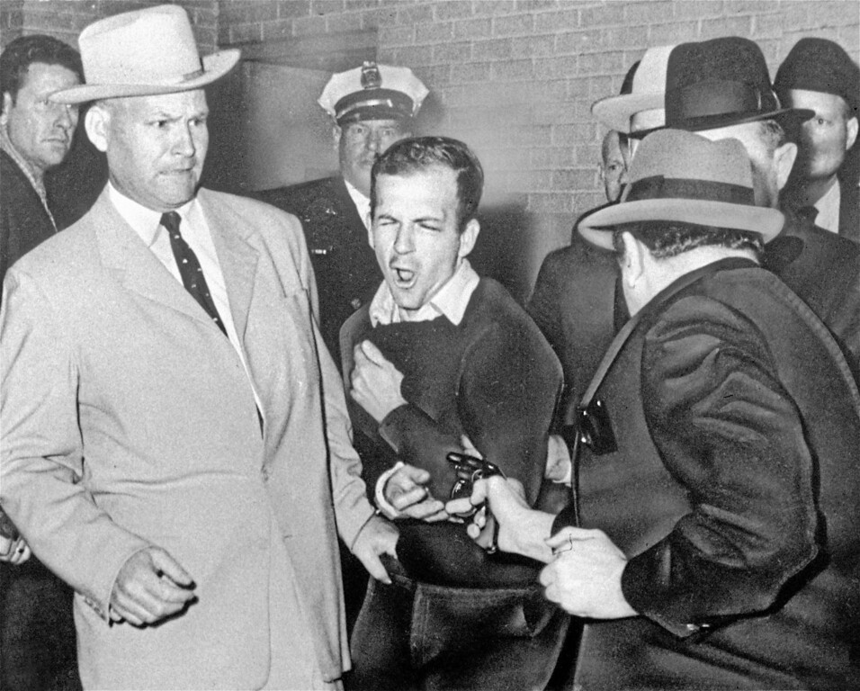 . Lee Harvey Oswald, accused assassin of President John F. Kennedy, reacts as Dallas night club owner Jack Ruby, foreground, shoots at him from point blank range in a corridor of Dallas police headquarters, in this Nov. 24, 1963 file photo.  Plainclothesman at left is Jim A. Leavelle. (AP Photo/FILE/Dallas Times-Herald, Bob Jackson)