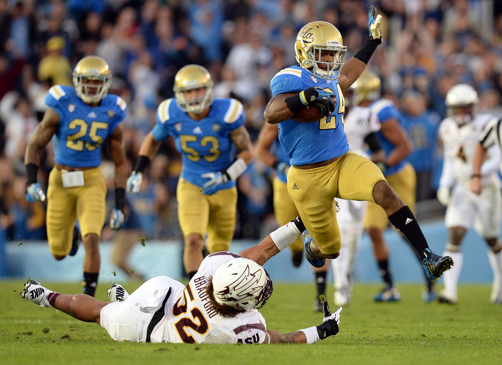 . UCLA�s Ishmael Adams #24 avoids the tackle of Arizona State�s Carl Bradford #52 during their game at the Rose Bowl Saturday November 23, 2013. Arizona State beat UCLA 38-33. (Photos by Hans Gutknecht/Los Angeles Daily News)