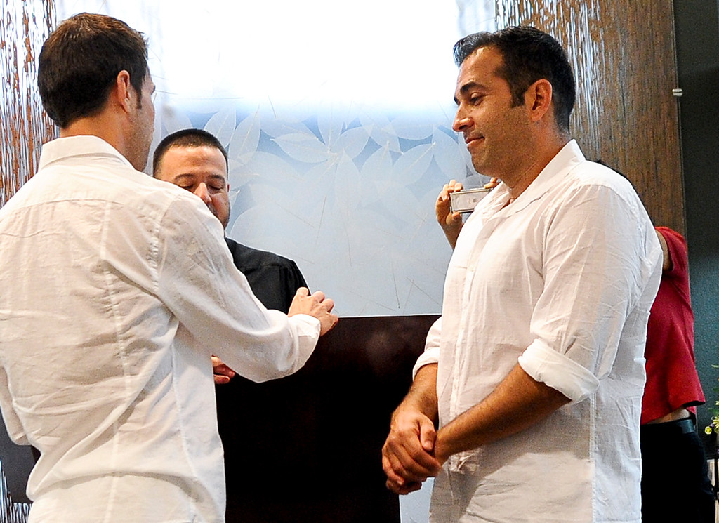 . Ken Bencomo, 45, right, and his partner of 10 yrs, Christopher Persky, 32, left, both of Rancho Cucamonga, get married at the San Bernardino County Hall of Records in San Bernardino on Monday, July 1, 2013. Bencomo was fire from his teaching position at a St. Lucy\'s Catholic School days after he married his gay partner in San Bernardino civil ceremony. (Rachel Luna / Staff Photographer)