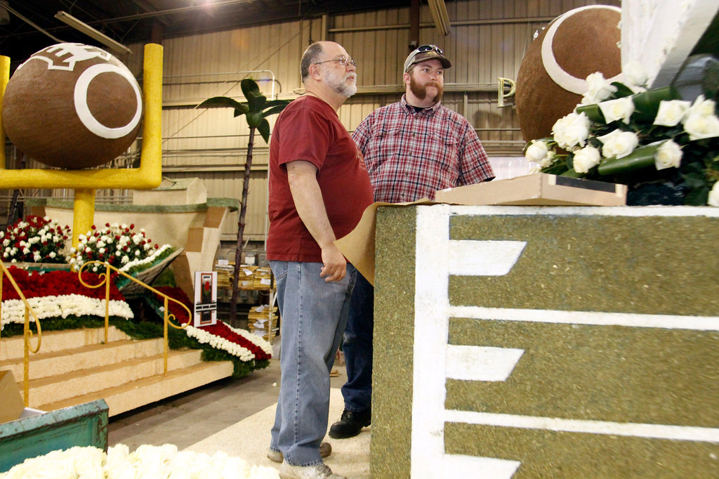 """. Jon Olson, with his son Andrew Olson, of Claremont, right, check out  the details that still need to be finished on the Michigan State\'s 2013 Tournament of Roses Parade Float, at the Artistic Entertainment Services in Azusa, CA., Tuesday, December 31, 2013. Jon Olson a \""""float operator\"""" has been driving Rose Parade floats for years, this year he has been chosen to drive the Michigan State float. (Photo by James Carbone for the Daily Bulletin)"""
