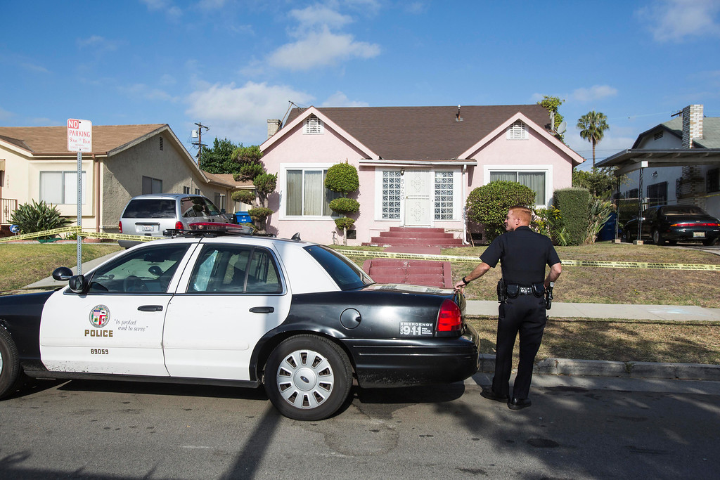 """. A police officer stands guard in front of the home of actor Michael Jace on Tuesday, May 20, 2014, in Los Angeles.  Jace, who played a police officer on the hit TV show \""""The Shield,\"""" was arrested on suspicion of homicide after his wife was found shot to death in their Los Angeles home, authorities said. Police arrived at the couple\'s home around 8:30 p.m. Monday after a report of shots fired, Officer Chris No said. April Jace, 40, was found dead inside, officials said.  Jace was taken into custody and booked early Tuesday on suspicion of homicide, No said. He was being held in a Los Angeles jail in lieu of $1 million bail.   (AP Photo/Ringo H.W. Chiu)"""
