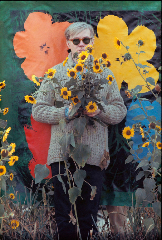 ". In this 1964 photo provided by Allen Cooper Enterprises, artist Andy Warhol stands in a field of sunflowers Susans in New York. The image was featured in an exhibit entitled: ""Before They Were Famous: Behind the Lens of William John Kennedy,\"" which opened on April 19th at the Site/109 gallery in New York. (AP Photo/William John Kennedy via Allen Cooper Enterprises)"