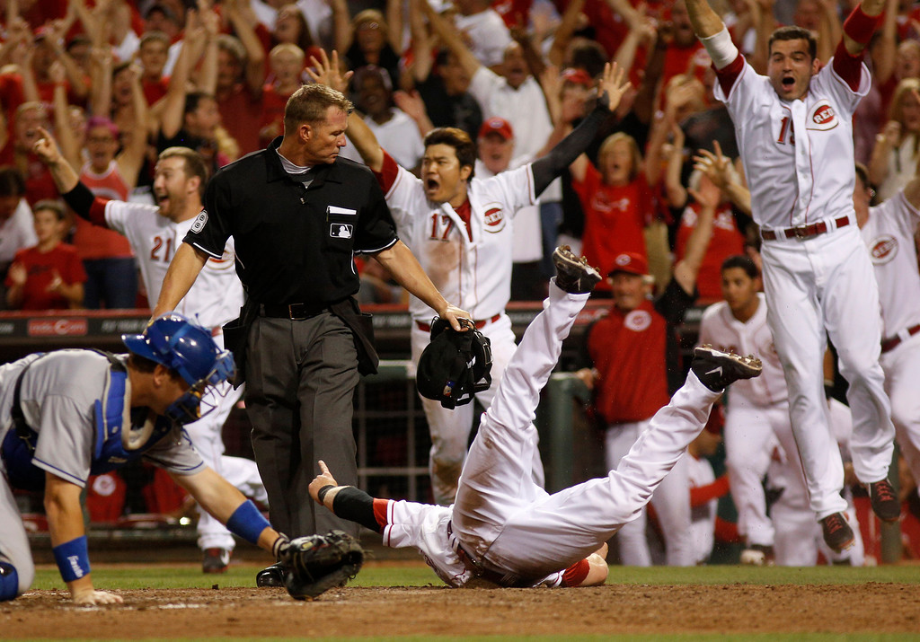 . Cincinnati Reds\' Zack Cozart, bottom right, slides into home plate scoring the winning run past Los Angeles Dodgers catcher A.J. Ellis, bottom left, in the ninth inning during a baseball game, Sunday, Sept. 8, 2013, in Cincinnati. The Reds won 3-2. (AP Photo/David Kohl)