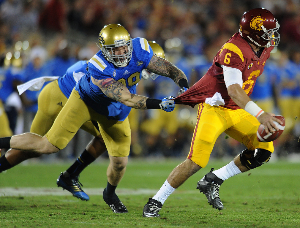 . UCLA QB Cody Kessler escapes the grasp of UCLA Cassius Marsh  in the first quarter. UCLA and USC played in a matchup of cross town rivals at the Los Angeles Memorial Coliseum in Los Angeles, CA.  photo by (John McCoy/Los Angeles Daily News)