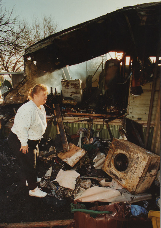 . A woman looks through the rubble of there burned trailer house in Sylmar, CA. 1/18/1994, photo by (John McCoy/Los Angeles Daily News)