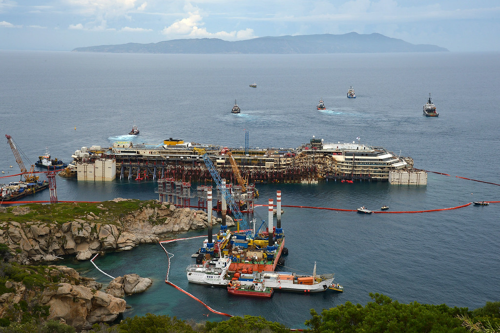 . A general view shows the wreck of the Costa Concordia cruise ship and tug boats during an operation to refloat the boat on July 14, 2014 off the Giglio Island. Over two and a half years after it crashed off the island of Giglio in a nighttime disaster which left 32 people dead, the plan is to raise and tow away the 114,500-tonne vessel in an unprecedented and delicate operation for its final journey to the shipyard where it was built in the port of Genoa.            (VINCENZO PINTO/AFP/Getty Images)