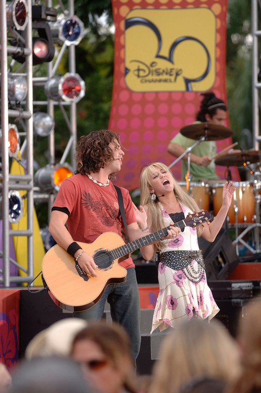 """. Disney Channel star Miley Cyrus, right, performs in concert as \""""Hannah Montana,\"""" her character from the Disney Channel hit series of the same name, with her band at Disney\'s Typhoon Lagoon water park at Walt Disney World in Lake Buena Vista, Fla., Thursday, June 22, 2006.  (AP Photo/Disney, Kent Phillips) ** NO SALES **"""