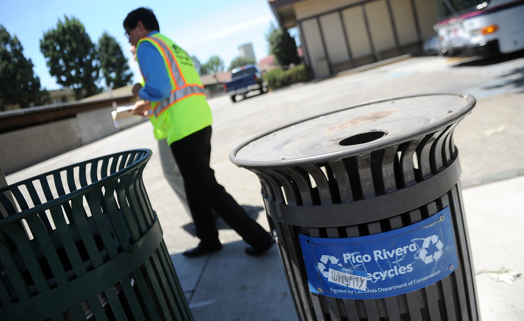 . Interns Monserrat Marquez, left, a former El Rancho graduate along with Robert Sanchez a La Serna graduate walk past a trash can after inspecting it next to a bus stop at the corner of Passons Blvd and Jackson Street as part of the Pico Rivera college prep program on Tuesday, July 16, 2013 in Pico Rivera, Calif.   (Keith Birmingham/Pasadena Star-News)