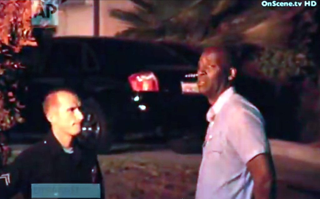 """. In this image taken from video from OnScene.tv, actor Michael Jace, right, is detained by police outside his home in Los Angeles on Monday night, May 19, 2014. Jace, who played a police officer on the hit TV show \""""The Shield,\"""" was arrested on suspicion of homicide after his wife was found shot to death in their Los Angeles home, authorities said. (AP Photo/OnScene.tv)"""