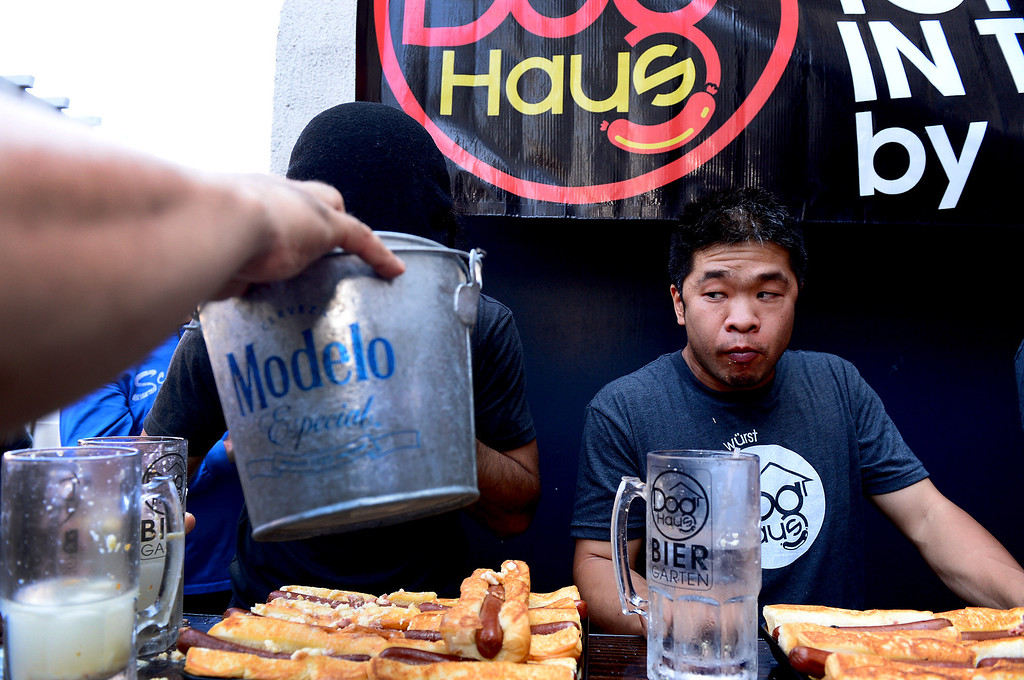 . Naader Reda, of Victorville, and Jimmy Lin compete in the First Annual Hot Dog Eating Competition at Dog Haus Biergarten in Old Pasadena Saturday, July 6, 2013. Jimmy Lin won after eating 11 dogs, 3 during a tiebreaker. (SGVN/Staff Photo by Sarah Reingewirtz)
