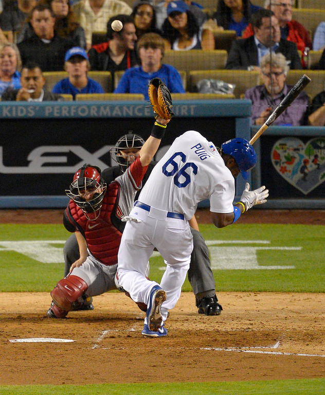 . Los Angeles Dodgers\' Yasiel Puig, right, is hit by a pitch as Arizona Diamondbacks catcher Miguel Montero catches during the sixth inning of their baseball game, Tuesday, June 11, 2013, in Los Angeles.  (AP Photo/Mark J. Terrill)