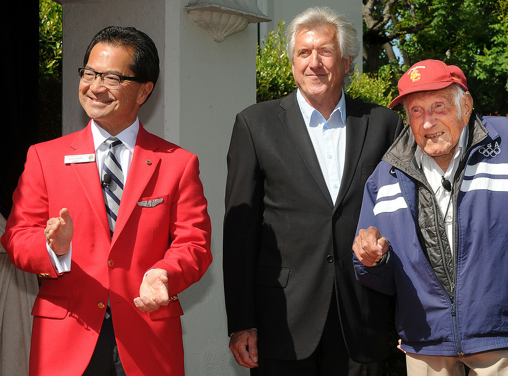 . Tournament President Richard L. Chinen, left, Luke Zamperini son of Louis Zamperini, right, listening to USC band  playing USC music after Louis Zamperini , who attended USC, was selected 2015 Tournament of Roses Grand Marshal. Olympian and World War II prisoner of war, Louis Zamperini, a true American Hero who survived excessive hardships. (Photo by Walt Mancini/Pasadena Star-News)
