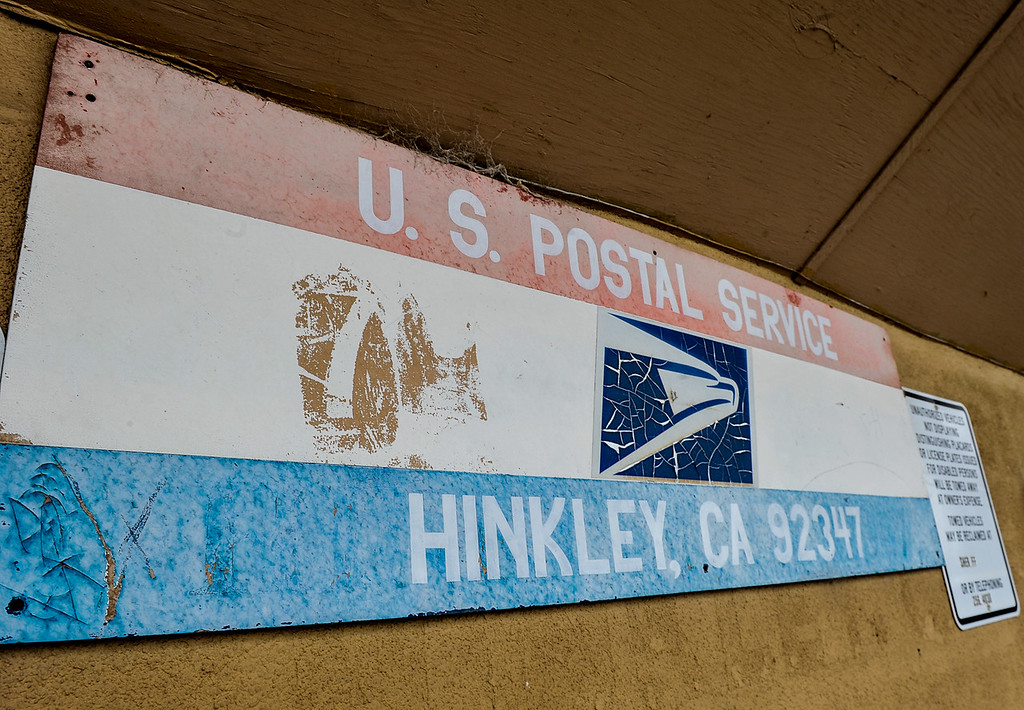 . A worn U.S. Postal Service sign is displayed in front of the post office in Hinkley, Calif. on Thursday, March 7, 2013. Over the past five years, the number U.S.P.S home deliveries has dropped from about 647 to 447. (Rachel Luna / San Bernardino Sun)