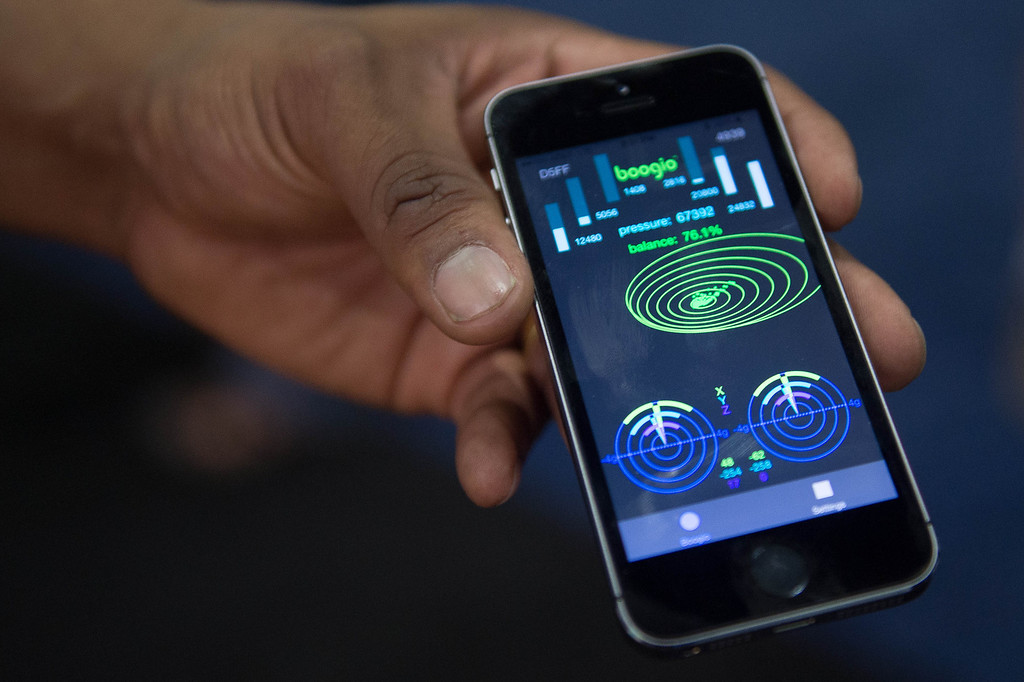 . Jose Torres shows the display data on an iPhone from his Boogio, a tech product worn in shoes, at Electronic Entertainment Expo in Los Angeles on Tuesday, June 10, 2014. (Photo by Watchara Phomicinda)