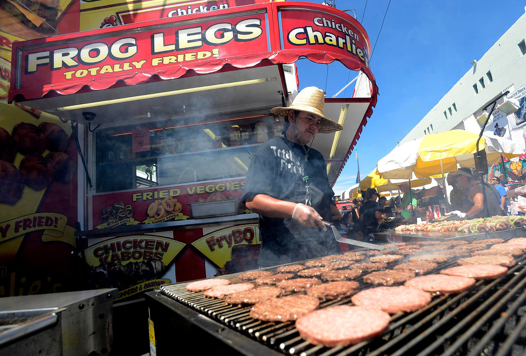 . Ernesto Ojeda, 19, of San Diego, faces the flames as he cooks burgers during Labor Day weekend at the 91st Annual Los Angeles County Fair in Pomona September 1, 2013.  When it comes to working in the heat, different jobs at the Fair bring different challenges.  GABRIEL LUIS ACOSTA/STAFF PHOTOGRAPHER.