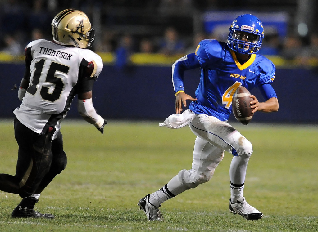 . Bishop Amat quarterback Koa Haynes (C) (4) scrambles past Alemany\'s Tyree Thompson (15) in the first half of a prep football game at Bishop Amat High School in La Puente, Calif., on Friday, Oct. 25, 2013.    (Keith Birmingham Pasadena Star-News)