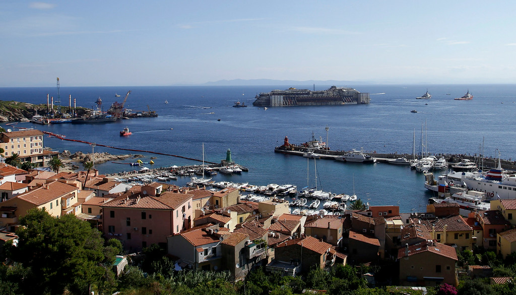. The wreck of the Costa Concordia cruise ship is maneuvered into position to be towed away from the tiny Tuscan island of Isola del Giglio, Italy, Wednesday, July 23, 2014. After more than two years since it slammed into a reef along the coastline of Isola del Giglio the wreck has begun its last journey, to the Italian port of Genoa, where it will be scrapped. 32 people died in the incident, one body is still missing. (AP Photo/Gregorio Borgia)