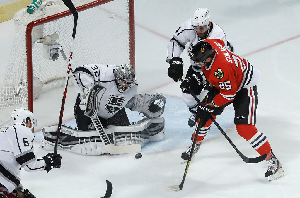 . Los Angeles Kings goalie Jonathan Quick (32) blocks a shot attempt by Chicago Blackhawks left wing Viktor Stalberg (25) as Kings center Dwight King (74) helps defend during the first period in Game 1 of the NHL hockey Stanley Cup Western Conference finals Saturday, June 1, 2013, in Chicago. (AP Photo/Charles Rex Arbogast)