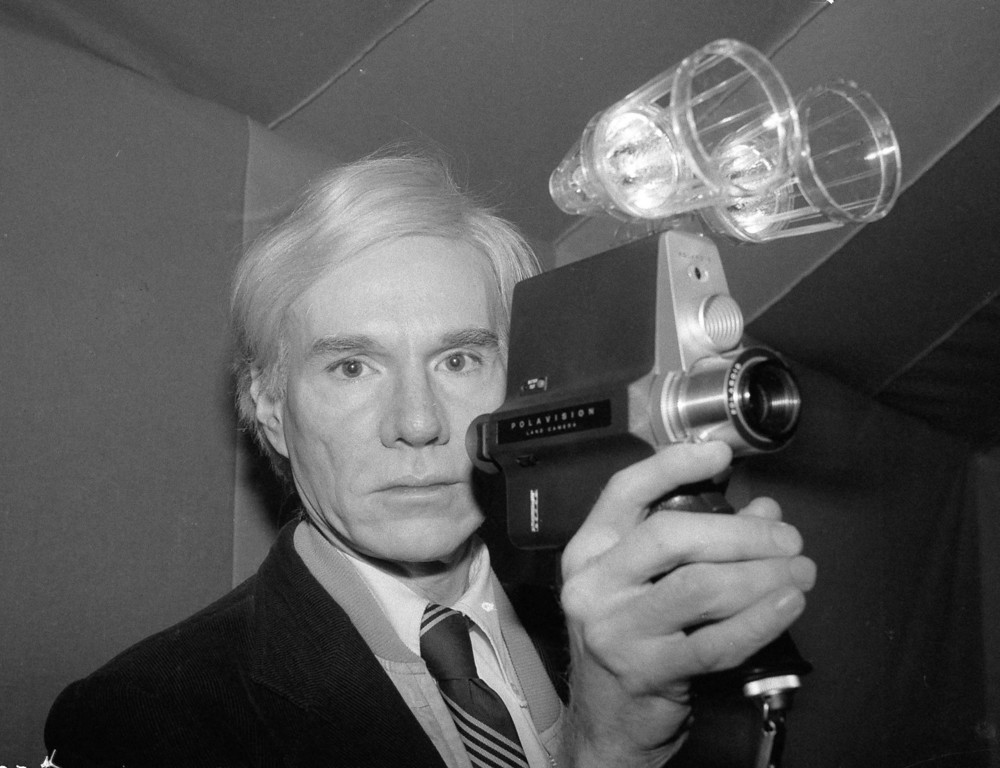 . Artist and underground filmmaker Andy Warhol poses with one of Polaroid\'s new film cameras, the Polavision camera, which features instant replay on television screens, Feb. 1, 1978. (AP Photo/Dave Pickoff)