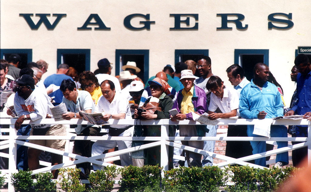. Horseplayers pour over their betting options, which included the debut of the $1 superfecta on 4/21/93.   (Los Angeles Daily News file photo)