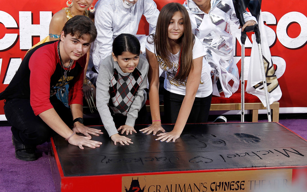 """. Paris, right, Prince, left, and Blanket Jackson put their hands in cement during the hand and footprint ceremony honoring their father, musician Michael Jackson, in front of Grauman\'s Chinese Theatre in Los Angeles, Thursday, Jan. 26, 2012. The ceremony was held to celebrate the \""""Michael Jackson The Immortal World Tour\"""" by Cirque du Soleil.  (AP Photo/Matt Sayles)"""