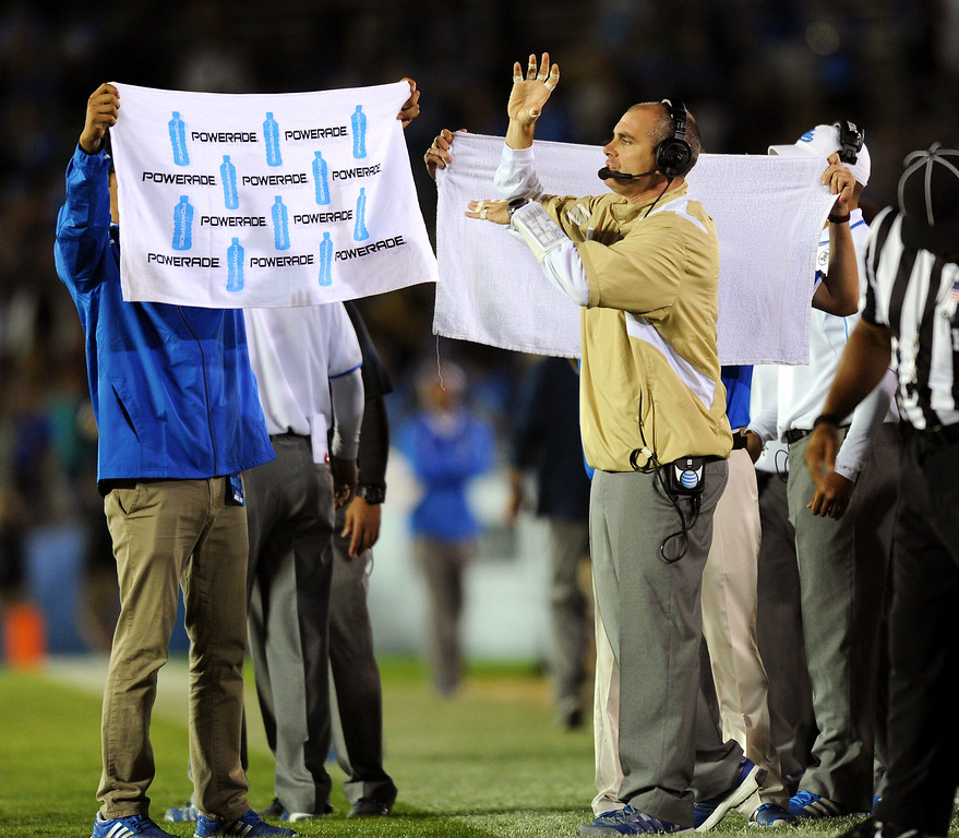 . UCLA defensive coordinator Lou Spanos signals his defense behind a curtain of towels against Colorado, Saturday, November 2, 2013, at the Rose Bowl. (Photo by Michael Owen Baker/L.A. Daily News)