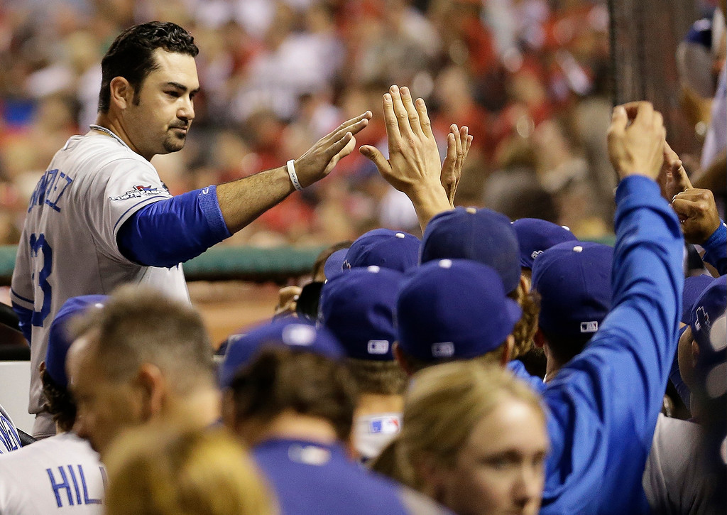 . Los Angeles Dodgers\' Adrian Gonzalez is congratulated in the dugout after scoring during the third inning of Game 1 of the National League baseball championship series against the St. Louis Cardinals Friday, Oct. 11, 2013, in St. Louis. (AP Photo/David J. Phillip)