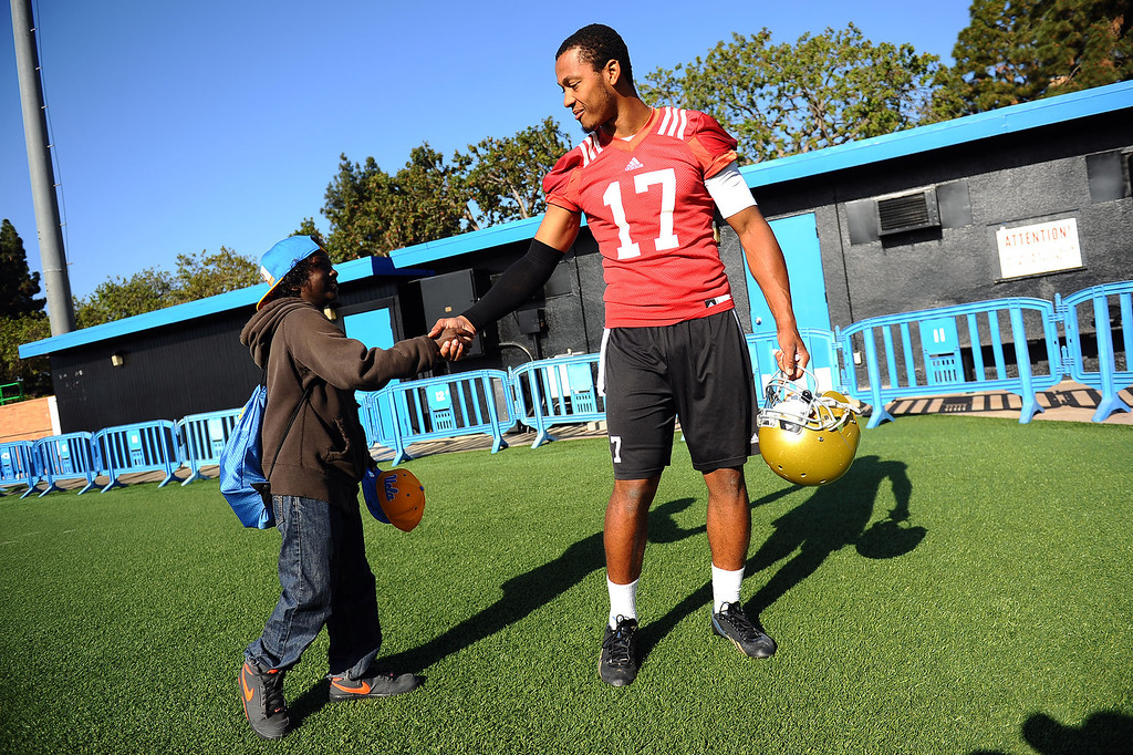 . UCLA Quarterback Brett Hundley greets a young fan following the final day of spring practice Thursday, April 24, 2014.(Andy Holzman/Los Angeles Daily News)