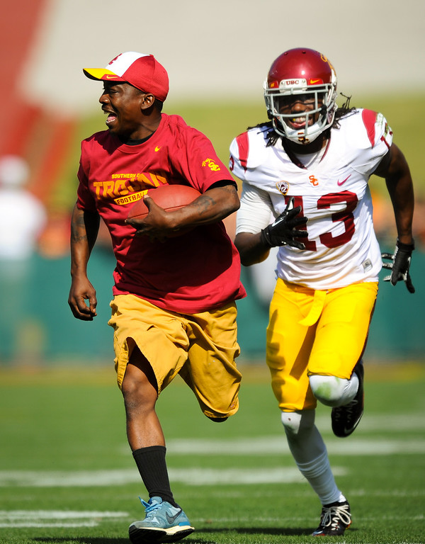 . USC fan Vernon Harris gets into the game for a reception as DB Kevon Seymour pursues at the spring game. (Photo by Michael Owen Baker/L.A. Daily News)