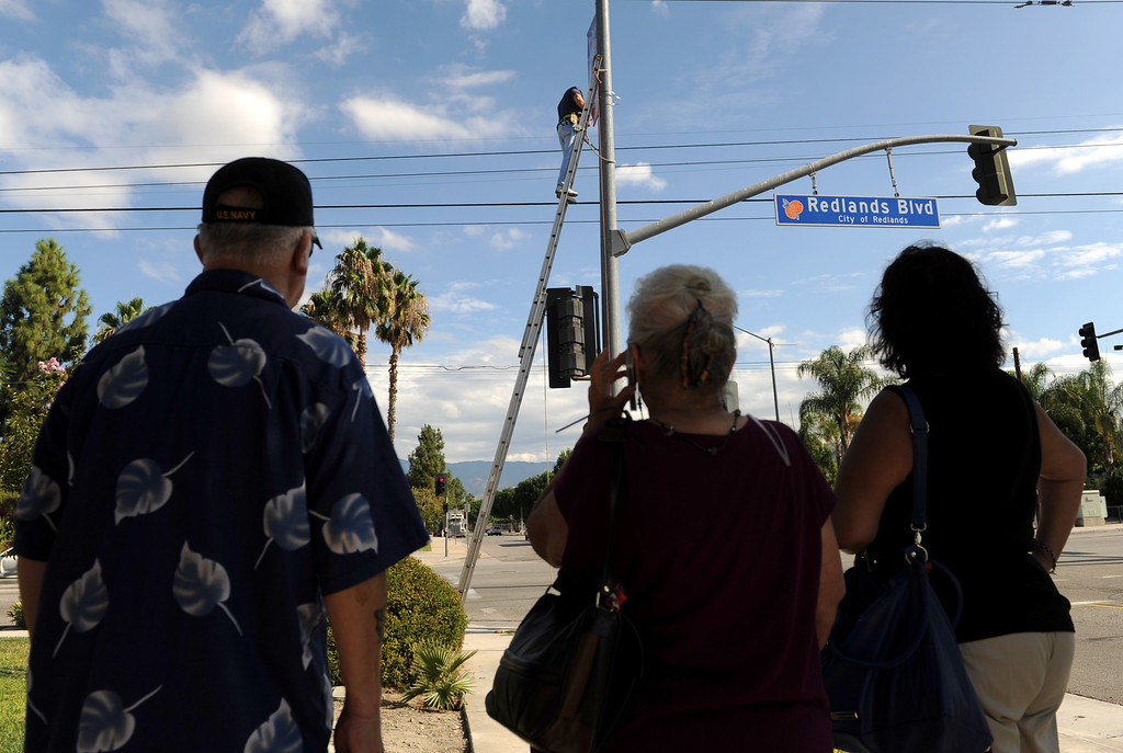 . (John Valenzuela/Staff Photographer) Family members of Samantha Kelly watch as Redlands Evening Kiwanis Club member Jerry Linkhart , hangs a Hometown Heroes banner of Kelly, a Naval officer from Redlands, at the corner of New Jersey St. and Redlands Blvd., Tuesday, August 27, 2013. Kelly is a E-5 Air Traffic Controller stationed in San Diego, an is a 2006 Redlands East Valley grad.