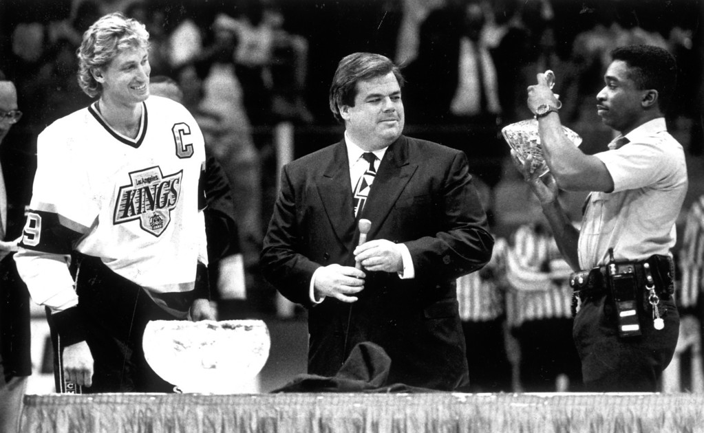 . Wayne Gretzky, left, admires the gold American eagle coins he received from Bruce McNall, center, during a ceremony before Kings\' game on October 17, 1989.   L.A. Daily News file photo