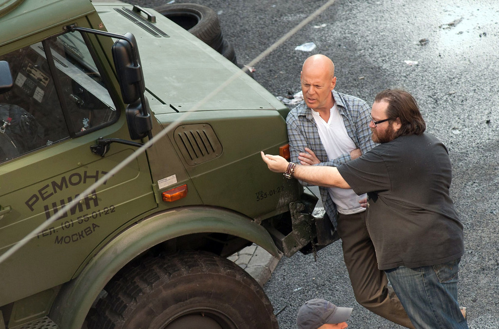 ". In this photo made available Tuesday, June 19, 2012, US actor Bruce Willis playing the role of John McClane, left, listens to Irish director John Moore, right, next to a Russian military jeep during shooting of the movie ""A Good Day to Die Hard\"", the fifth part of the \""Die Hard\"" series in Budapest, Hungary, Monday, June 18, 2012. (AP Photo/MTI, Bea Kallos)  (Movie released on January 31, 2013)"