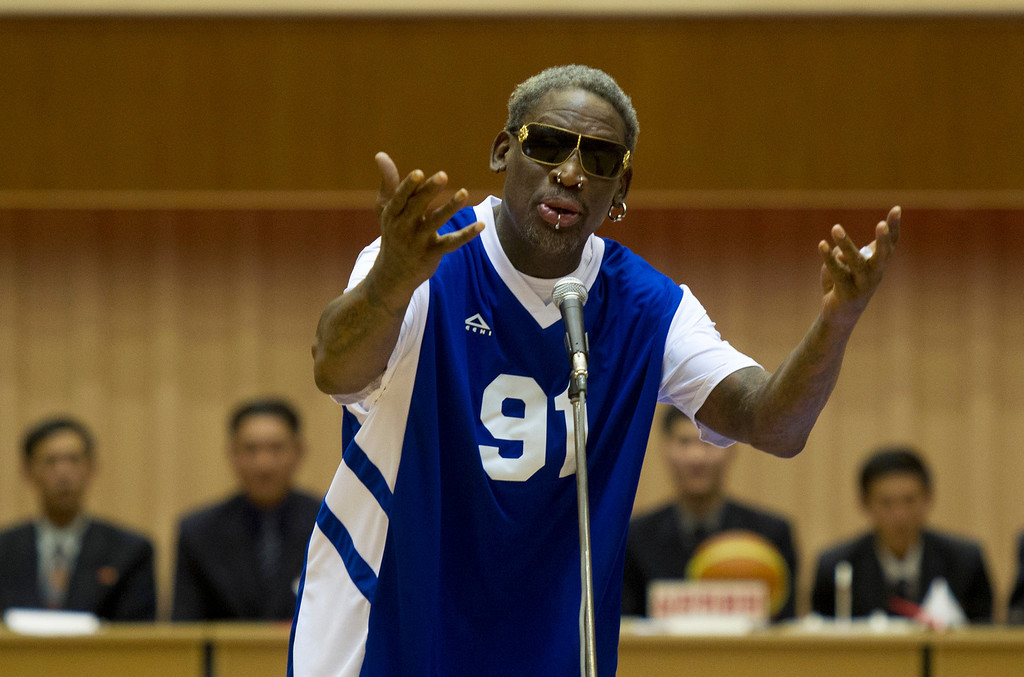 . Dennis Rodman sings Happy Birthday to North Korean leader Kim Jong Un, seated above in the stands, before an exhibition basketball game at an indoor stadium in Pyongyang, North Korea on Wednesday, Jan. 8, 2014. (AP Photo/Kim Kwang Hyon)